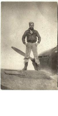 Standing on top of a British fighter found crashed in the desert.